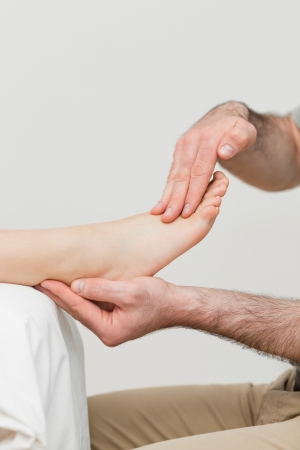 Practitioner holding the foot of a patient in a room photo