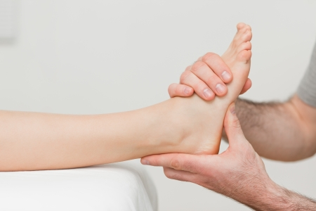 foot doctor: Hands of an osteopath massaging a foot in a room