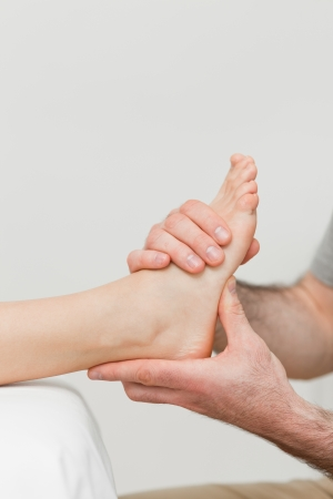 Hands of a physiotherapist massaging a foot in a room photo
