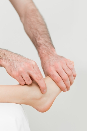 neuromuscular reeducation: Physiotherapist touching the foot of a patient in a room Stock Photo