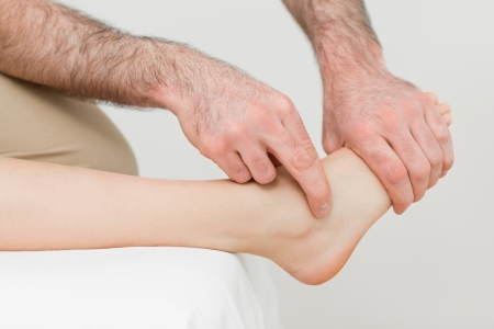 muscle retraining: Hands of a physiotherapist massaging the foot of a patient in a room