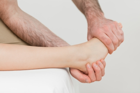 neuromuscular reeducation: Osteopath holding the ball of the foot of a patient in a room