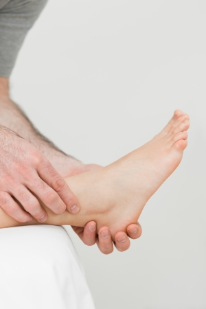 Ball of a foot being held by a practitioner in a room Stock Photo - 16202574