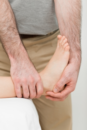 neuromuscular reeducation: Foot being manipulated by a practitioner in a room Stock Photo