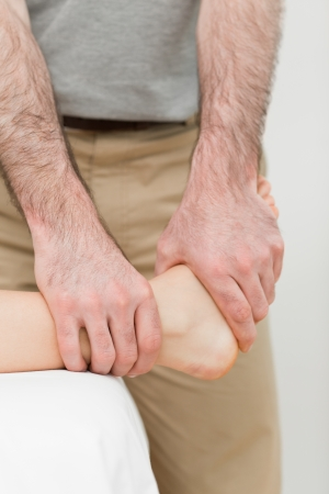 neuromuscular reeducation: Osteopath manipulating the ankle of a patient in a room