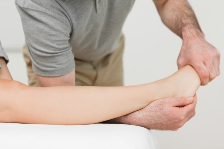 Physiotherapist stretching the ankle of a patient in a room Stock Photo - 16204935