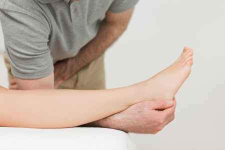Serious physiotherapist working on an ankle in a room Stock Photo - 16204648