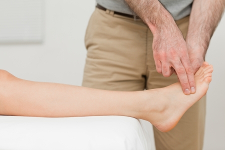 Fingers of a physiotherapist touching a foot in a room Stock Photo - 16204393