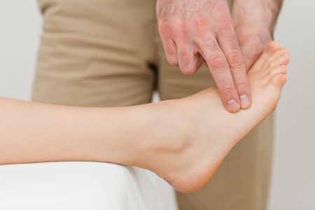 neuromuscular reeducation: Fingers of a physiotherapist pressing on a foot in a room