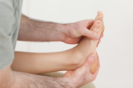 Osteopath holding the ball of a foot in a room Stock Photo - 16204766
