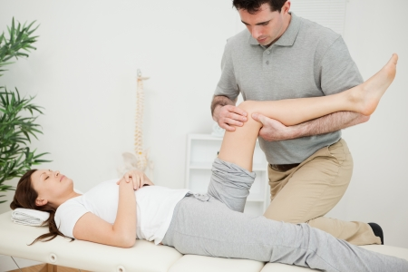 joint mobilization: Serious osteopath bending the leg of a patient in a room Stock Photo
