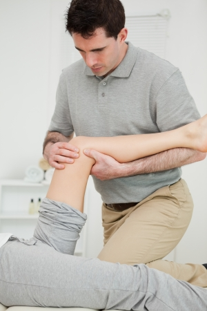 Serious physiotherapist looking at the knee of a patient in a room photo