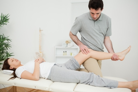 abductor: Peaceful brunette woman lying on a medical table in a physio room