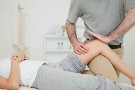 neuromuscular reeducation: Serious osteopath massaging the knee of a patient in a room