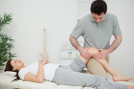 kneecap: Black-haired osteopath touching the knee of a patient in a room Stock Photo