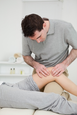 Physiotherapist pressing on the knee of a patient indoors Stock Photo - 16208033
