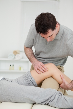 Serious practitioner holding the knee of a patient in a medical room Stock Photo - 16207730
