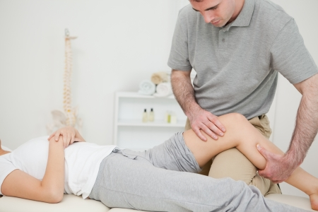 Seus doctor holding the leg of a woman in a room Stock Photo - 16207386