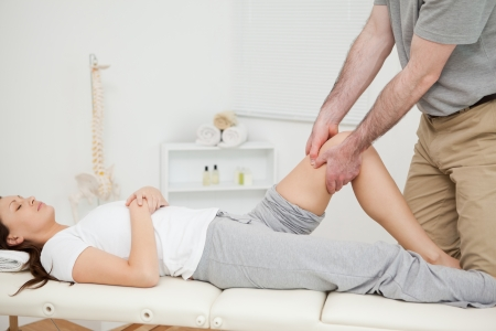 lower limb: Peaceful woman lying while being manipulated in a medical room