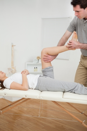 lower limb: Serious osteopath bending the leg of a woman in a room Stock Photo