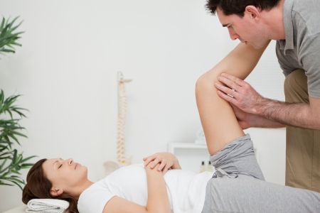 Serious physiotherapist raising a leg in a room Stock Photo - 16205016