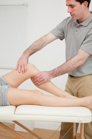 Serious brunette doctor holding the knee of his patient in a room Stock Photo - 16207188