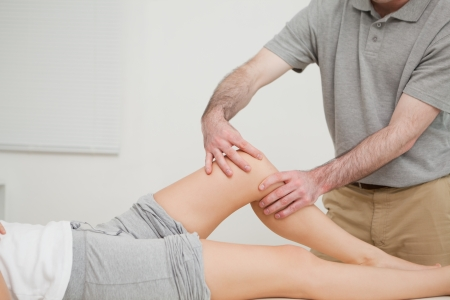 lower limb: Knee of a woman being massaged by a physiotherapist in a room