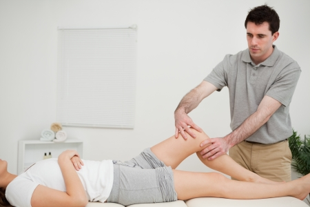 lower limb: Serious doctor holding the knee of a woman in a room