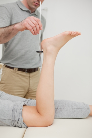 Seus practitioner using a reflex hammer in a medical room Stock Photo - 16204607