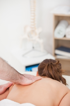 spinal conditions: Woman being massaged while lying on the belly in a room