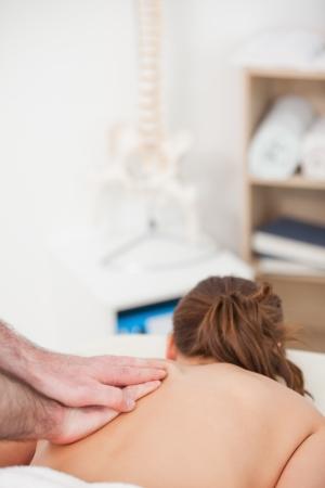 spinal manipulation: Retro della donna che viene massaggiata da un massaggiatore in una stanza