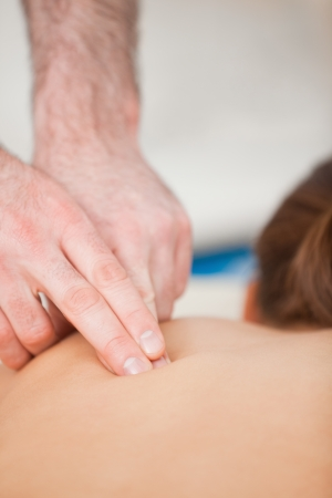 spinal manipulation: Doctor using his finger to massaged the back of his patient in a room
