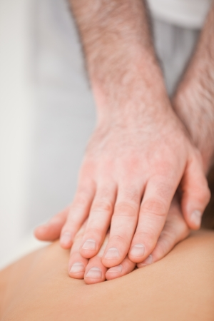 Osteopath massaging his patient while pressing his back in a room photo