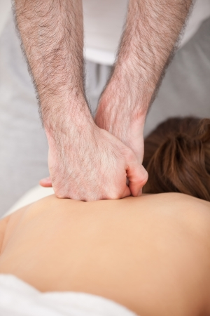 spinal conditions: Doctor massaging the back of his patient while using the back of his hand in a room