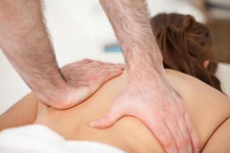 spinal conditions: Woman lying on the belly while being massaging with two hands of doctor indoors