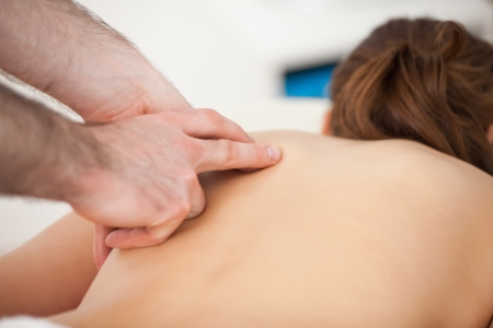 trapezius: Doctor massaging his patient while using only two fingers in a room