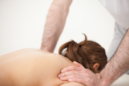 spinal conditions: Doctor massaging the shoulders of woman while standing in a room Stock Photo