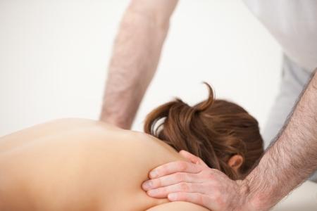 spinal manipulation: Dottore massaggiare le spalle della donna in piedi in una stanza