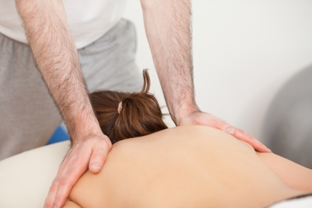 Shoulders of woman being massaged by doctor in a room photo