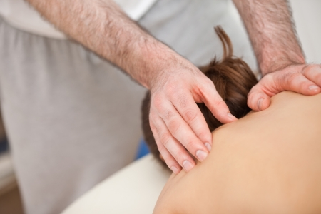 spinal conditions: Chiropractor touching the back of his patient in a room Stock Photo