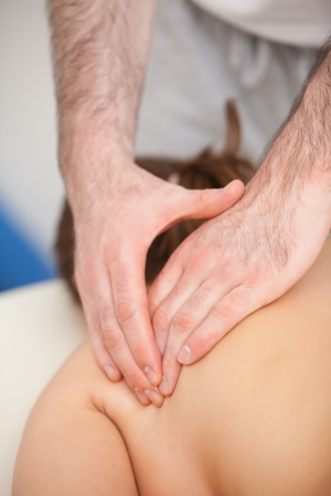 spinal conditions: Doctor pressing the side of the back of his patient while standing indoors Stock Photo