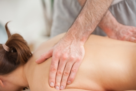 spinal conditions: Woman lying on the belly while being massaged on his back in a room Stock Photo