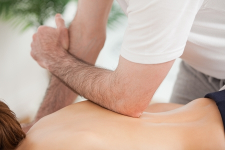 spinal conditions: Doctor massaging his back of his patient while using his elbow in a room Stock Photo