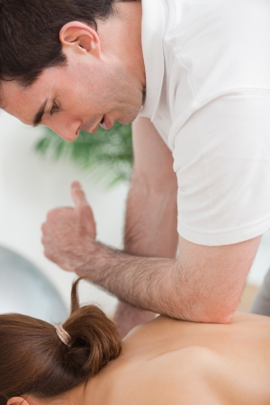back sprains: Back of woman being massaged by the elbow of doctor in a room