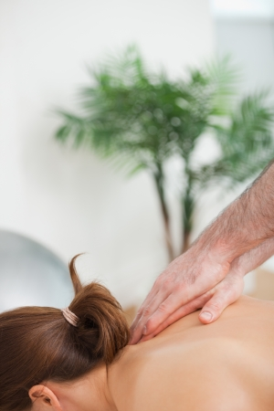 back sprains: Practitioner massaging the top of back of his patient indoors Stock Photo