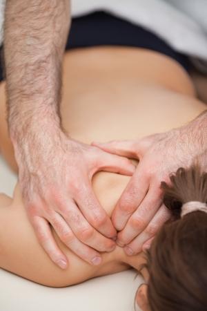 spinal manipulation: Osteopata premendo le spalle del suo paziente durante l'utilizzo al chiuso i suoi due mani