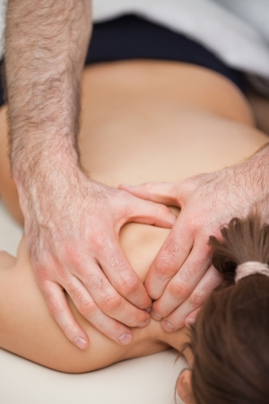 back sprains: Osteopath pressing the shoulders of his patient while using his two hands indoors