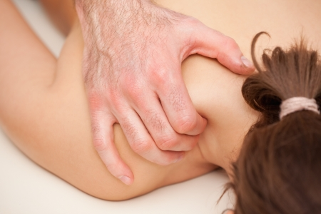 back sprains: Chiropractor squeezing the shoulder of woman while massaging indoors Stock Photo