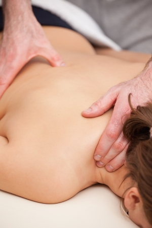 spinal manipulation: Doctor standing while massaging his patient in a room