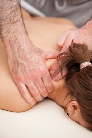 back sprains: Shoulders of woman being squeezed while lying on a table in a room